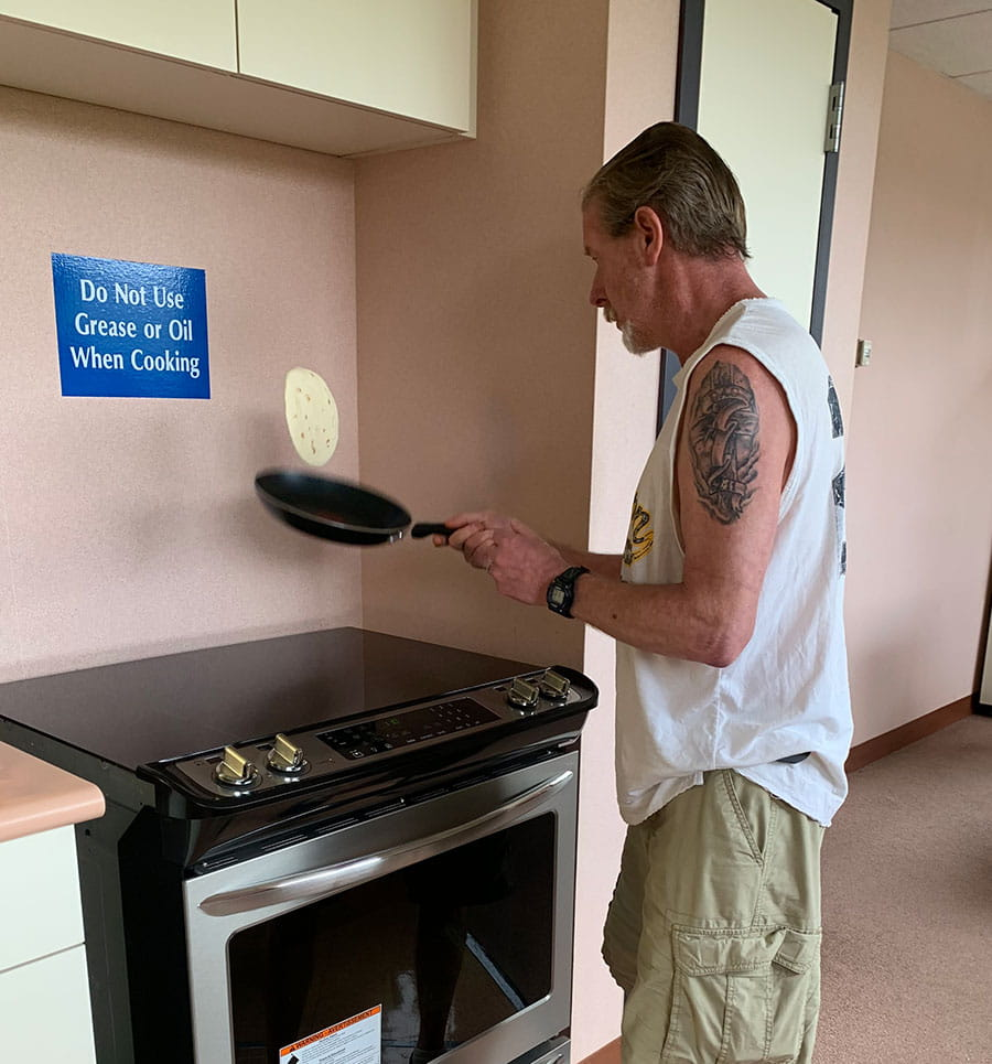 Phil May 2019: A patient flips a tortilla in the neuropsych rehab kitchen.