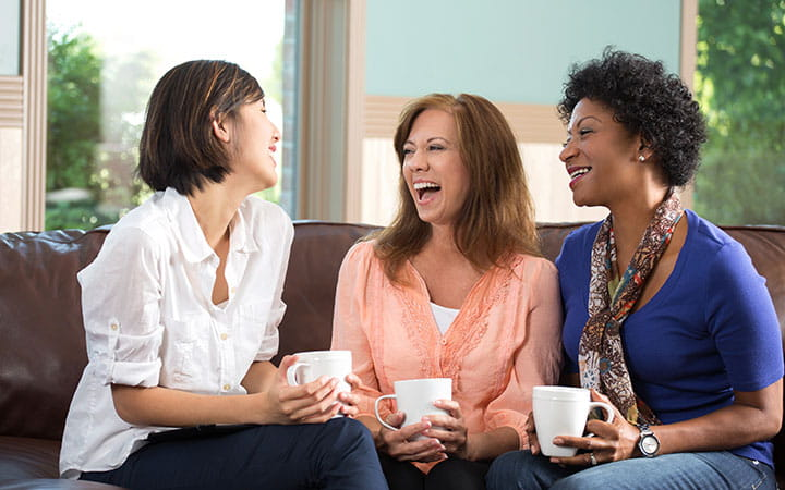 three women laughing with coffee cups
