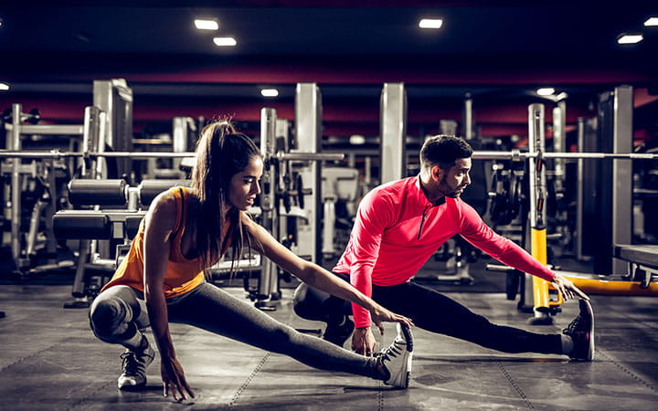 man and woman stretching hamstrings