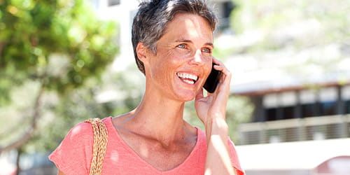A smiling mature woman talking on cellphone outdoors