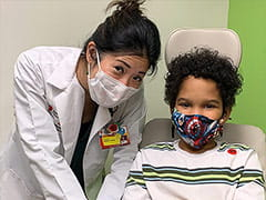 Dr. Lynn Woo and Trey are all smiles behind the masks