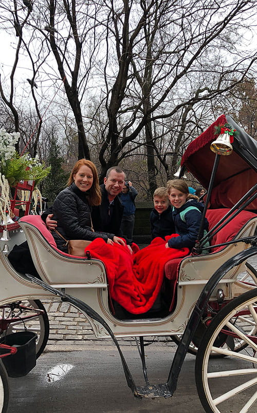 Darby Harris and family riding in a horse-drawn carriage