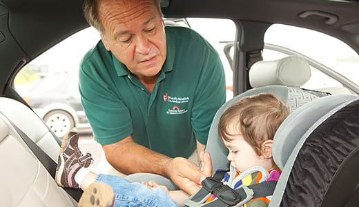 Man buckling a child into a car seat.