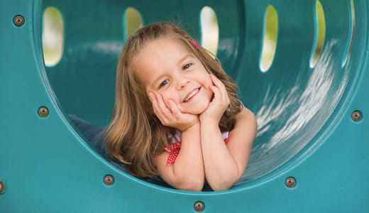 Girl inside a playground tunnel.