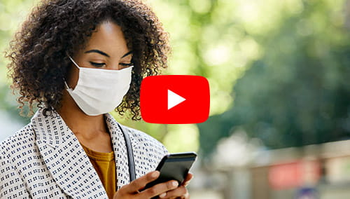 Businesswoman using smart phone while wearing protective face mask