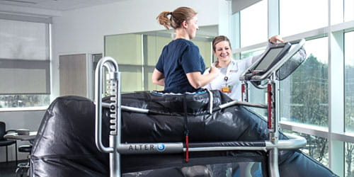 Female physical therapist talking with female patient on treadmill